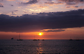 Big Island, Hawaii. Sunset with red sun and sky with dark clouds above over water with boats on it.