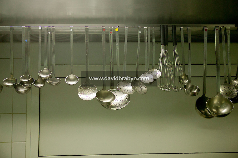 Metal ladles and spoon hang from above in a kitchen at the Gregoire Ferrandi cooking school in Paris, France, 17 December 2007.