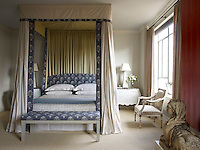 In the master bedroom, the bed hangings, bench and headboard are all upholstered in matching C&C Milano linen. The limestone sphinx is from the owner's shop, Fleur