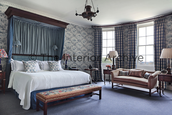 A blue and white themed bedroom with large print gingham curtains and an unusual wallpaper featuring hunting hounds within a leafy trellis work
