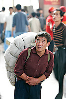 Migrant workers from poorer provinces in China shown inside the Beijing railway station in Beijing, China. Many workers come to the larger cities to find better paying work as laborers, construction workers rather than being poorly paid farmers..24 Sep 2005