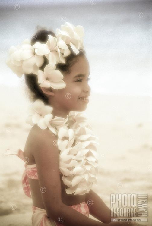 Young Hawaiian girl with plumeria lei on beach