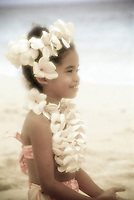 Young Hawaiian girl with plumeria lei on beach