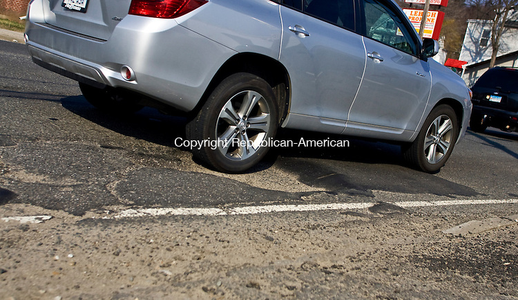 NAUGATUCK, CT - 21 MARCH 2010 -032110JT02-<br /> A car drives into a pothole at the intersection of Hanover Street and Chase Avenue in Waterbury on Sunday.<br /> Josalee Thrift Republican-American