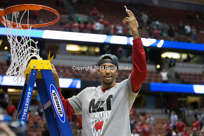 Wisconsin Badgers Jordan Hill cuts down a piece of the net after the Western Regional Final NCAA college basketball tournament game against the Arizona Wildcats Saturday, March 29, 2014 in Anaheim, California. The Badgers won 64-63 (OT). (Photo by David Stluka)