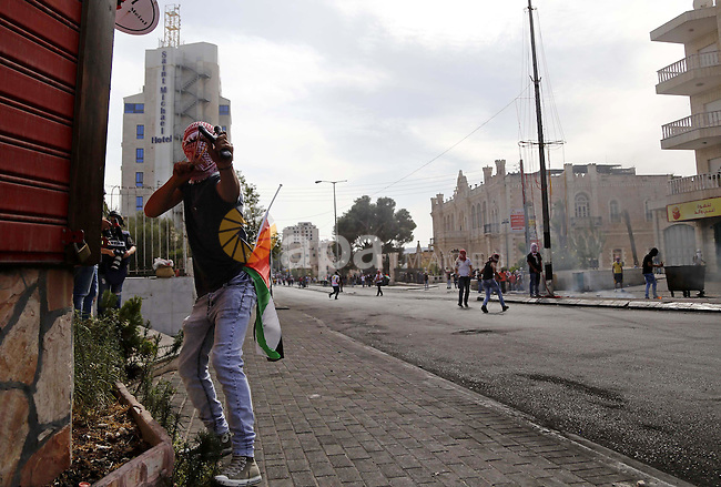 A Palestinian protester uses a sling shot to throw stones at Israeli security forces during clashes in the West Bank city of Bethlehem, on October 13, 2015. A wave of stabbings that hit Israel, Jerusalem and the West Bank this month along with violent protests in annexed east Jerusalem and the occupied West Bank, has led to warnings that a full-scale Palestinian uprising, or third intifada, could erupt. The unrest has also spread to the Gaza Strip, with clashes along the border in recent days leaving nine Palestinians dead from Israeli fire. Photo by Muhesen Amren