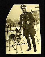 BNPS.co.uk (01202 558833)<br /> Pic: Mullocks/BNPS<br /> <br /> Ullrich Ellenbeck who collected the signature in his Army Officer uniform with one of his dogs dated 1943.<br /> <br /> A rare signed postcard of Adolf Hitler which he presented to one of his guards because of their mutual love of dogs has emerged for auction.<br /> <br /> Hitler gave Ullrich Ellenbeck this postcard of him relaxing in a suit with his German Shepherd Blonda and signed the postcard with the name 'wolf' which he only did very rarely for close friends and associates.<br /> <br /> Hitler often referred to himself as Herr Wolf and would say 'I am the wolf and this is my den'.<br /> <br /> He saw wolves as strong and ruthless in his image and described the SS as his 'pack of wolves'.<br /> <br /> Ellenbeck was an SS guard at the Berghof who worked with the guard dogs there and and it was a conversation about their respective dogs which prompted Hitler to sign the postcard.