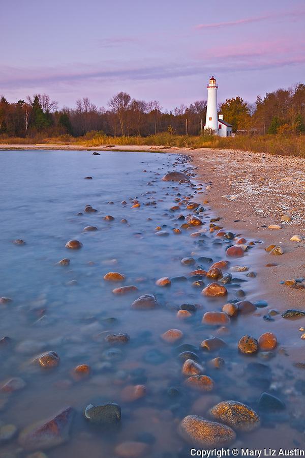 Alcona County, MI: Sunrise light on Sturgeon Point Lighthouse (1870)  on Lake Huron in autumn