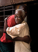 Pastor Morie S. Ngobeh embraces one of the boys at the 'City of Rest', a rudimentary counselling and mini rehabilitation centre for recovering drug addicts, alcoholics and traumatised or delinquent youths.  Pastor Ngobeh runs the centre and attributes the its success to the extensive rest, food and prayer. © Fredrik Naumann Freetown, Sierra Leone.