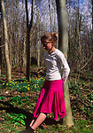 ADFRWD Young girl in leaning against a tree in daffodils in springtime