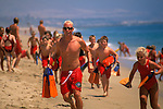 Kids running on sand beach as exercise training for Junior Lifeguard Camp, Balboa Island, Newport Beach, California
