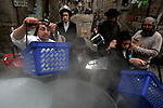 Traditionally-dressed, religious Jews ritually purify dishes and pots in vats of boiling water on a street corner in the ultra-Orthodox neighborhood of Mea Shearim, Jerusalem, April 6, 2009. In the days leading up to the Passover holiday, observant Jews purge their houses of bread and other leavened foods which are not consumed during the eight-day holiday commemorating the Israelites' Exodus from Egypt. Photo by: Daniel Bar On/JINI