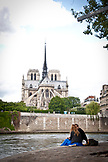 FRANCE, Paris, a couple is sitting on the Seine river bank, Notre Dame in the background