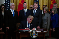 United States President Donald J. Trump signs a trade agreement between the United States and China in the East Room of the White House in Washington D.C., U.S., on Wednesday, January 15, 2020.  <br /> <br /> Credit: Stefani Reynolds / CNP/AdMedia