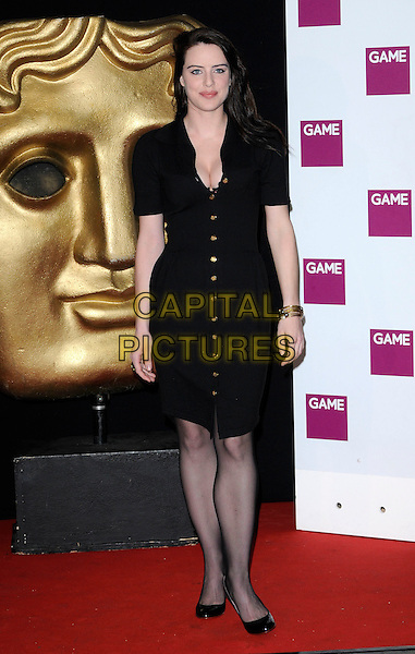 MICHELLE RYAN .At the British Academy Video Games Awards, London HIlton Hotel, Park Lane, London, England, UK, March 19th 2010..BAFTA full length black shirt dress gold brass buttons cleavage tights shoes patent gold bangles bracelets .CAP/CAN.©Can Nguyen/Capital Pictures