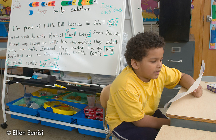 MR/Schenectady, New York.Zoller School- Inclusion classroom (urban, public, elementary school)/ Grade 1.Boy (6, African-American and Caucasian) reads over what he has written about bullying. White board behind him contains synopsis of class discussion..MR: Jen4.© Ellen B. Senisi