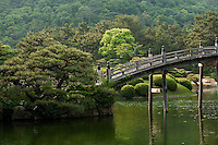 The delicately arched Enketsukyo, or Crescent Moon. bridge crossing the Nan-ko Pond on a late spring day at Ritsurin Koen, Takamatsu.