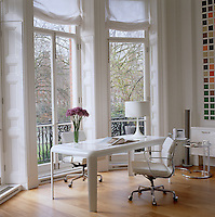 A white aluminium desk by Piero Lissoni and a pair of office chairs in front of the tall French windows of the living room