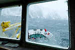 Ice covers the window of the Arctic expedition ship, Akademik Shokakskiy, while a figure sets the anchor on the bow. The ship was forced to take shelter in a bay during a storm off Baffin Island, Nunavut, Canada.