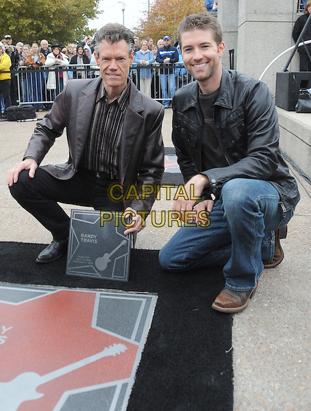 RANDY TRAVIS & JOSH TURNER .Poses for photographs with her star during the 2008 Music City Walk of Fame Inductiion Ceremony, Nashville, Tennessee, USA..November 9th, 2008.full length kneeling couching black plaque jacket jeans denim .CAP/ADM/MS.©Mike Strasinger/AdMedia/Capital Pictures.