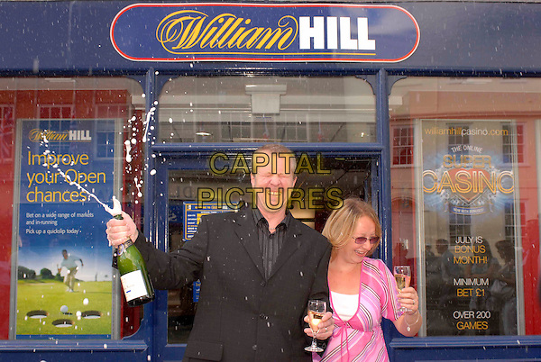 ADAM PHILLIPS (Aged 40)  & wife Sue (Aged 38) .Adam and Sue from Littlehampton, Sussex, have won £427,434 from William Hill bookmakers, after placing a £2.00 bet..Chichester, West Sussex,17th July 2007..half length cheque celebrating win gambling betting bookies champagne kissing.CAP/FIN.©Steve Finn/Capital Pictures.