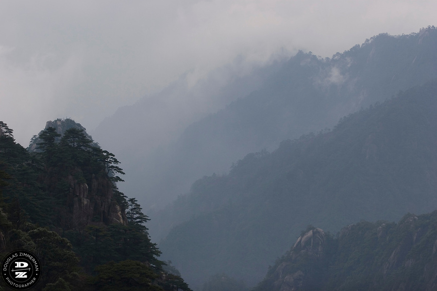 The Granite peaks and pine trees of Hung Shan mountain are enveloped in fog and low clouds.  Hung Shan mountain, in Anuhi province,  contains some of the most beautiful natural scenery in China.  Photograph by Douglas ZImmerman