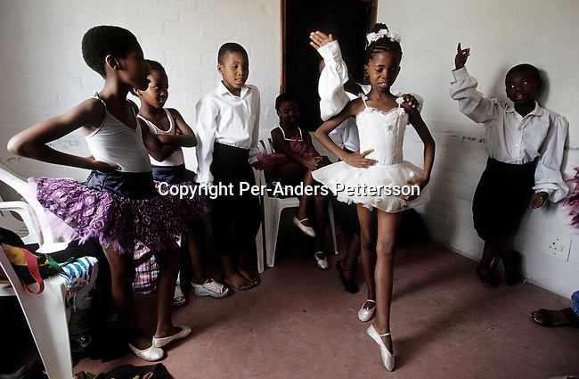 Eight-year-old Wongi Zoe (c) warms up before a yearly ballet performance on November 25, 2000 in Guguletu, a big township outside Cape Town, South Africa. About 200 children dance ballet in a school called Dance For All, which teaches unprivileged children dance after school. Many children are talented and the discipline taught during the dance classes has helped many to improve their concentration in school. The township is struggling with high unemployment, crime and high levels of HIV/Aids. (Photo by: Per-Anders Pettersson) ....