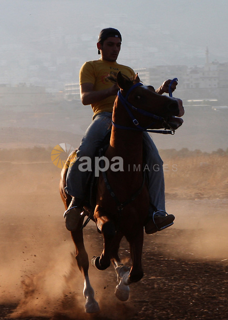 Palestinian jockeys ride their horses during a race in the West Bank city of Nablus on July 9, 2010. Hundreds of Palestinians from all over the West Bank gathered to follow the horse race on Friday in the northern West Bank city. Photo by Wagdi Eshtayah