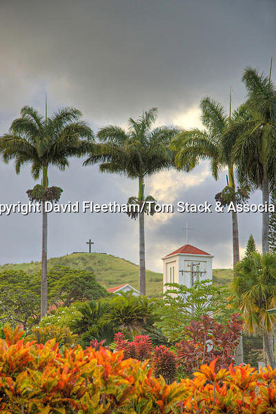 St. Mary's Catholic Church cross in front of the lava rock cross on a grassy hill overlooking Hana Town, Maui, Hawaii.