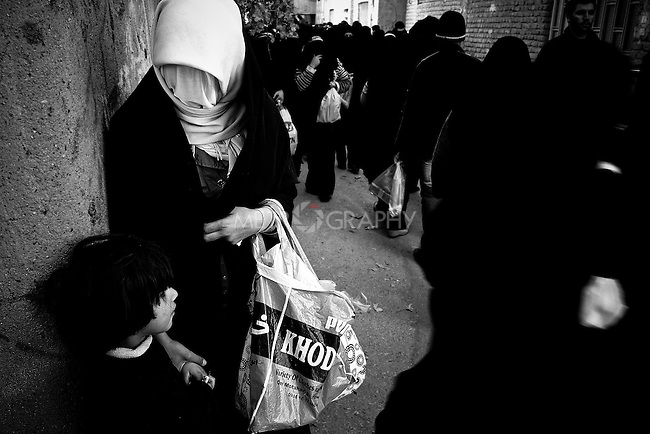 KHORRAMABAD, IRAN : A mother and her child during the festival of Ashura...Every year to mark the death of Imam Hussein, Shia Muslims mourn for two days. In Khorramabad and Lorestan in the west of Iran, during the first day of mourning, called Tasooa, women take a vow of silence and go through the streets with the children lighting candles. At 4 am on Ashura, the second day, men cover themselves in mud and then stand in front of a fire until the mud has dried to clay. After this they go to the mosque and pray...Photo by Farhad Babaei/Metrography