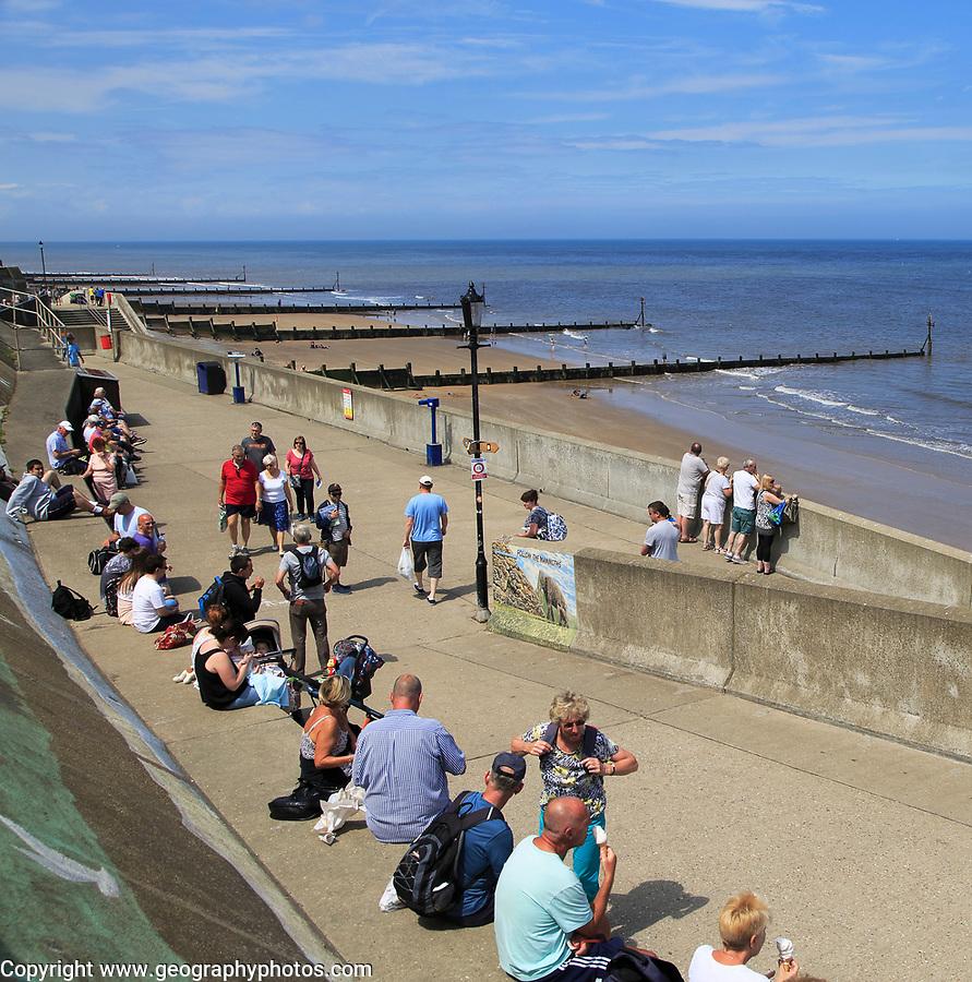 People on promenade sandy beach summer at Sheringham, Norfolk, England, UK