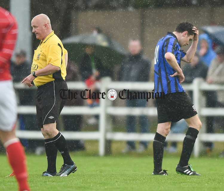 Bridge United player Darragh Fitzgerald leaves the pitch after being red carded by referee Martin O Brien during their Cup final against Newmarket Celtic at Doora. Photograph by John Kelly.