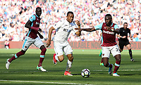 Jordan Ayew of Swansea City is challenged by Arthur Masuaku of West Ham United during the Premier League match between West Ham United and Swansea City at the London Stadium, England, UK. 08 April 2017
