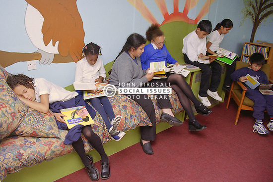 Primary school children reading books in library; one girl sleeping,