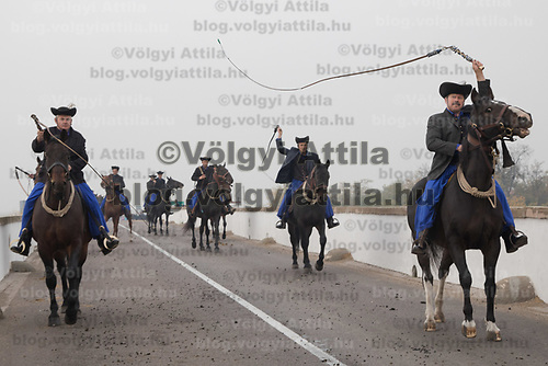 A group of herdsmen is seen using their whips crossing a bridge during a celebration of the end of the grazing season in the Great Hungarian Plains in Hortobagy, 200 km (124 miles) east of Budapest in Hortobagy, Hungary on Oct. 21, 2017. ATTILA VOLGYI
