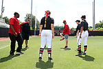 RALEIGH, NC - MAY 07: NC State head coach Shawn Rychcik (third from right) kicks a hacky sack before the game in a circle with members of the team staff and players. The North Carolina State University Wolfpack hosted the University of Louisville Cardinals on May 7, 2017, at Dail Softball Stadium in Raleigh, NC in a Division I College Softball game. Louisville won the game 7-0.