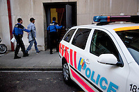 Switzerland. Geneva. Two police officers and a convict man enter the Paquis police station. The man was arrested while stealing articles in a department store. The inmate is an arab man from the Maghreb area. A police station or station house is a building which serves police officers and contains offices, locker rooms, temporary holding cells and interview/interrogation rooms. Both policemen are wearing a ballistic vest, bulletproof vest or bullet-resistant vest which is an item of personal armor that helps absorb the impact from knives, firearm-fired projectiles and shrapnel from explosions, and is worn on the torso. Soft vests are made from many layers of woven or laminated fibers and can be capable of protecting the wearer from small-caliber handgun and shotgun projectiles, and small fragments from explosives such as hand grenades. 15.03.12 © 2012 Didier Ruef..