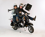 A young couple posed on a motor scooter on a white background.