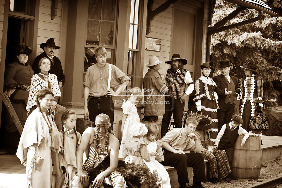 Historical depiction of several classes of people waiting on the train depot platform for the steam trains arrival