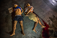 "MANILA, PHILIPPINES - OCTOBER 04: The bodies of two unidentified, alleged drug dealers, victims of a summary execution, lay on the pavement with their hands tied behind their backs and faces wrapped in packing tape, in front of the Santa Catalina Girl's College, Lagarda on October 4, 2016 in Manila City, Philippines. The victims were both found with cardboard placards with a warning reading ""Don't copy me - I'm a pusher"", and ""Don't copy me I'm a user, holder-upper and house robber"". CCTV footage was later discovered and shows the bodies of the men being dumped by the roadside in the early hours of the morning. Such messages are often found attached to the bodies of those killed in summary executions, unofficial murders that the government claims they have nothing to do with. They are a warning, left by supposed vigilantes, to strike fear into those who would use or sell drugs.<br /> Photo by Daniel Berehulak for The New York Times"