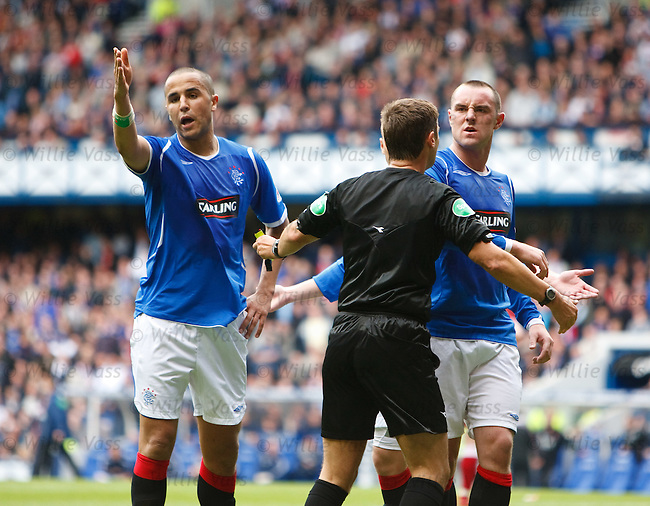 Referee Stuart Dougal sends off Madjid Bougherra and the Rangers players try to have a go at the linesman