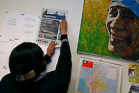 A journalist pins the front page of a Norwegian image to the wall. Main story is the violence in Burma. Democratic Voice of Burma is radio and TV station run by exiled Burmese. Opposing the government, the DVB has been transmitting, from the Norwegian capitol Oslo, into Burma since 1992.