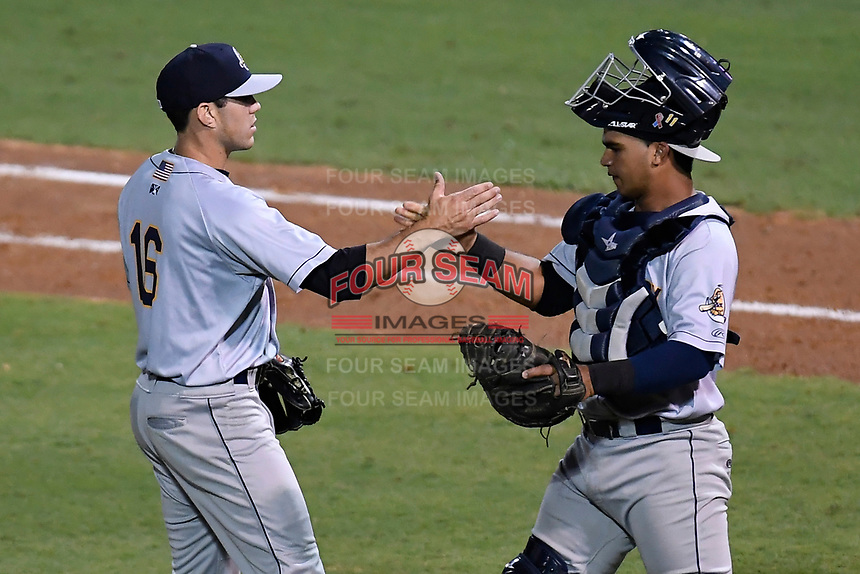Pitcher Matt Wivinis (16) of the Charleston RiverDogs slaps hands with catcher Eduardo Navas (11) after earning the save in Game 2 of the South Atlantic League Southern Division Playoff against the Greenville Drive on Friday, September 8, 2017, at Fluor Field at the West End in Greenville, South Carolina. Charleston won, 2-1, and the series is tied at one game each. (Tom Priddy/Four Seam Images)