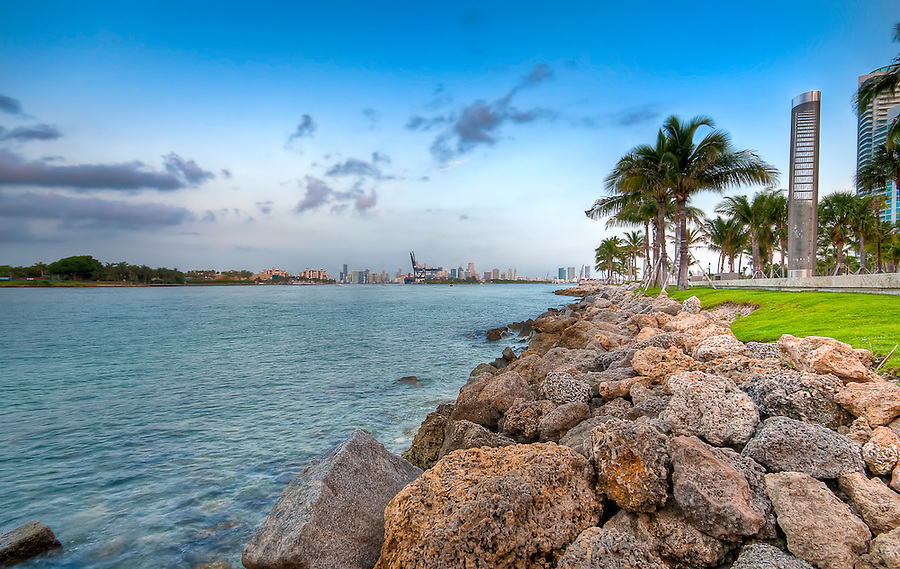 View of waterway used to enter Miami Seaport with city in the background and recreational park at the side.