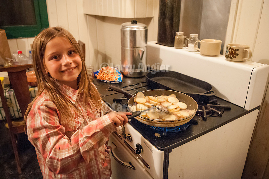 Night in the cabin during the fall cattle gathering in the High Sierra...Isabella Hobbs cooking potatoes on the stove