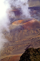 White clouds hover over a huge cinder cone composed of red sand inside the vast volcanic crater at Haleakala National Park on Maui.