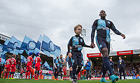 Aaron Pierre of Wycombe Wanderers heads onto the pitch with a match day mascot during the Sky Bet League 2 match between Wycombe Wanderers and Portsmouth at Adams Park, High Wycombe, England on 28 November 2015. Photo by Andy Rowland.