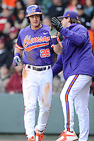 Left fielder Reed Rohlman (26) of the Clemson Tigers is congratulated after scoring the Tigers' only run in the first inning of the Reedy River Rivalry game against the South Carolina Gamecocks on Saturday, February 28, 2015, at Fluor Field at the West End in Greenville, South Carolina. South Carolina won, 4-1. (Tom Priddy/Four Seam Images)