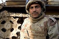 Iraqi tank gunner HAmmed Hussein from the 1st company, 1st armour battalion of the 1st mechanized Iraqi Army Brigade seeks cover in back of his tank  while conducting  patrols, check points and observation posts on code name route Michigan, the main road of Ramadi in the week during the national election on WED Dec 14 2005 in Ramadi, Iraq. 1st company is part of the first armor battalion of the New Iraqi Army. it has started its training in January 2005. after 50 days their 35 russian and chinese built T 55 tanks begun conducting operations under the guidance of a US military adivisor team. in April 2005 they patrolled in the Abu Ghraib area concluding their first significant mission. While these old tanks are rolling on the ramadi streets more modern T72s are getting ready to become fully operational in Taji, their main base. the Iraqi army wanted to show their power in ramadi during the Dec 15 elections displaying their new armour company. but like all the other Iraqi forces they are not going to secure the polling sites, staying in the rear with the rest of the iraqi and coalition forces. T 55s are very old tanks. production begun in the late 50s to the late 70s. athough obsolete many countries still use the T55 as their main heavy armoured combat vehicle. slow, heavvy and with very little room for the crew it suffers from many mechanical problems constantly challenging the iraqi mechanics and engineers.