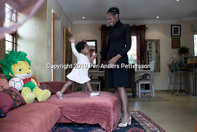 JOHANNESBURG, SOUTH AFRICA - MAY 17: Kagiso Msimango, plays with her daughter in her house on May 17, 2010, in Fourways, Johannesburg, South Africa. Kagiso is part of the new young generation of black South African's who has obtained a better education and opportunities than their parents. The country has seen a big increase in a black middle class since the end of Apartheid and democracy in 1994. Many can afford to take their children to private schools and take overseas holidays. (Photo by Per-Anders Pettersson)